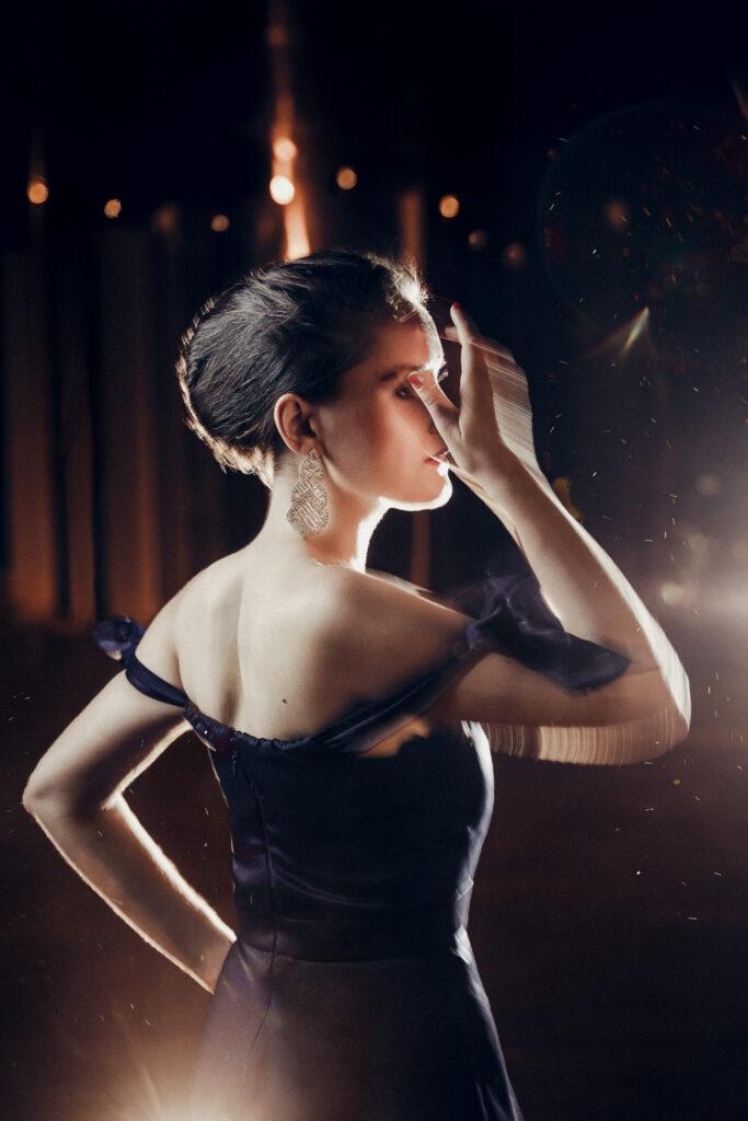 Yvonne Prentki in einem schwarzen Abendkleid allein auf der Bühne, die Seitenbühne ist im Hintergrund zu sehen.