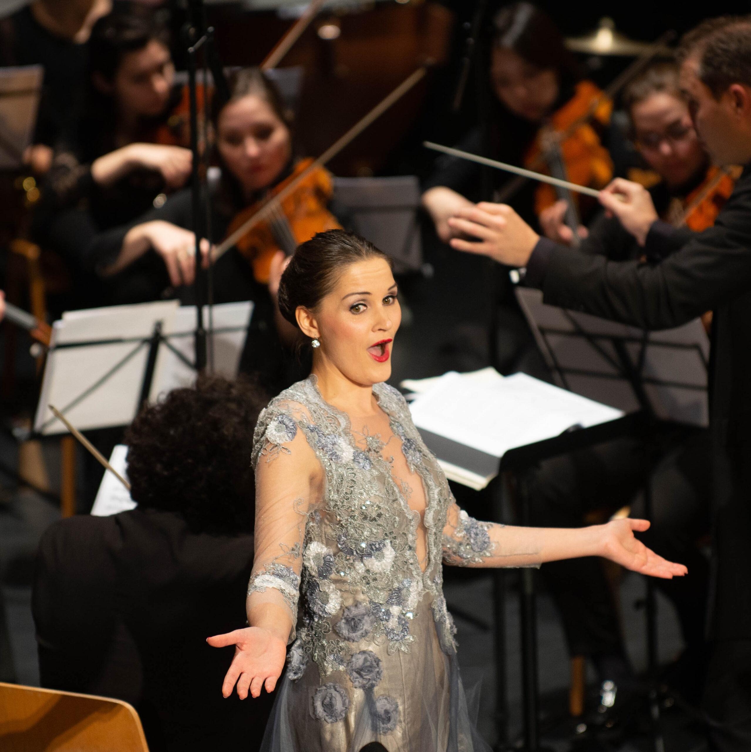 Yvonne Prentki in einem silbernen Konzertkleid vor Orchester und Dirigent im Scheinwerferlicht. Sie ist gerade dabei eine Arie zu singen.