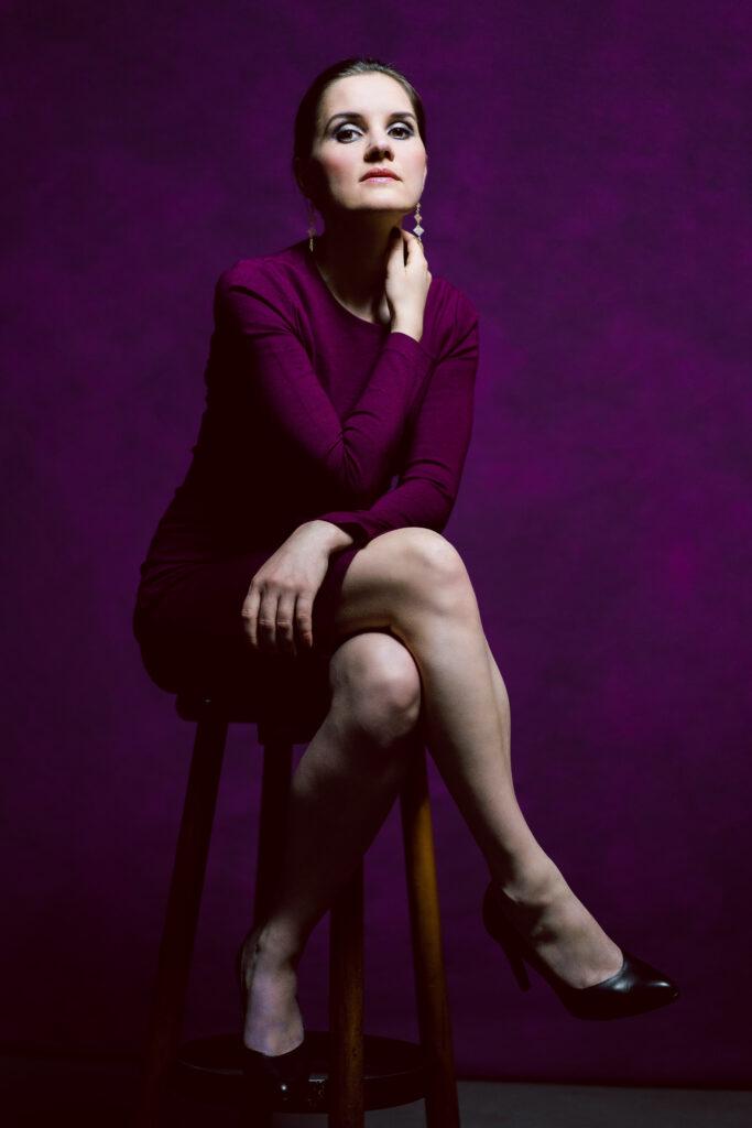 Sopranistin Yvonne Prentki bei einem Photoshooting in einem lila Etuikleid. Sie sitzt auf einem Barhocker in der Farbe Cognac. Der Hintergrund ist ebenso ein tiefes lila.