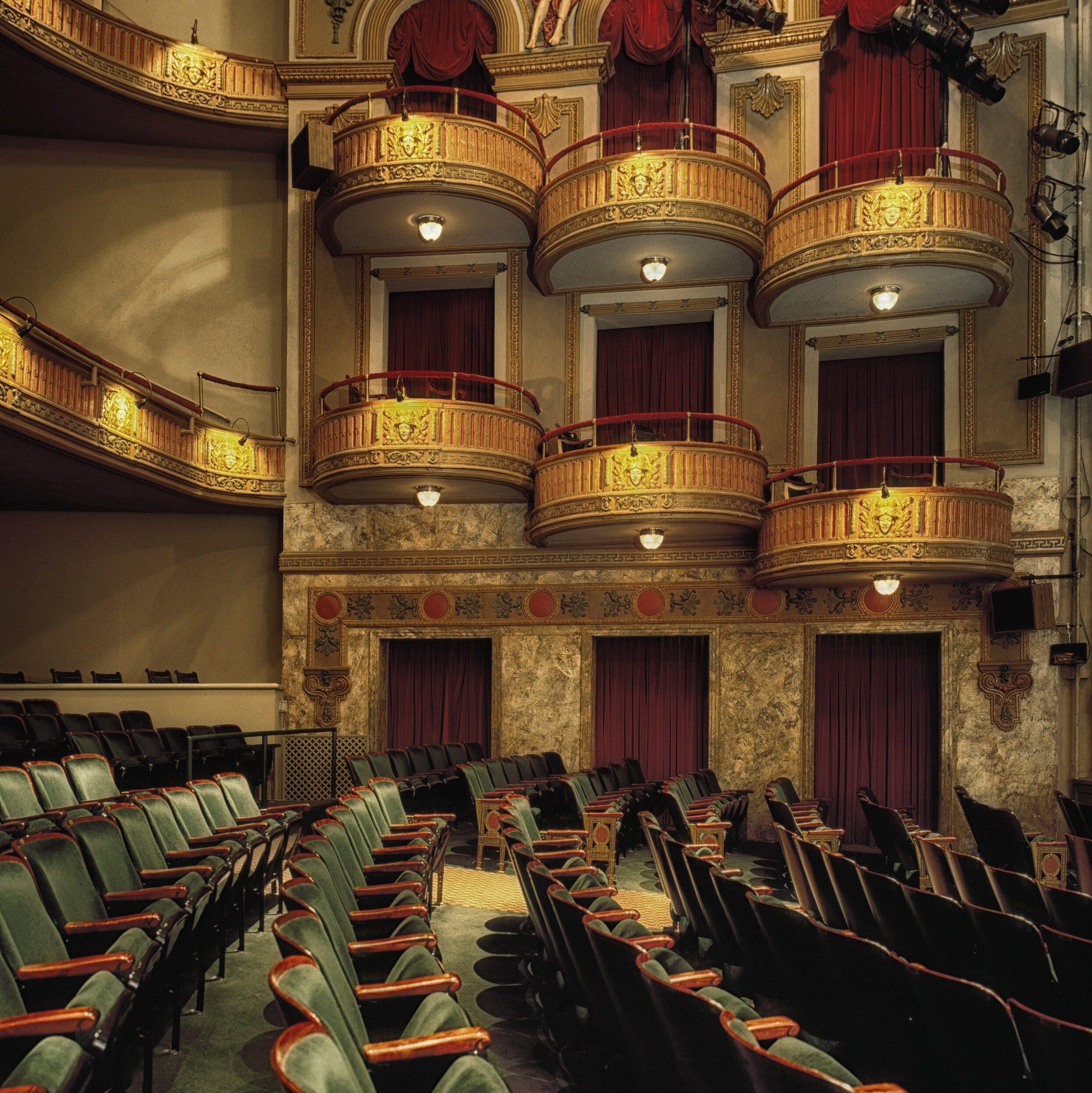 Der Zuschauerraum eines Theaters mit smaragdgrünen Sitzen in Samt und goldenen Rängen, sowie roten Vorhängen.